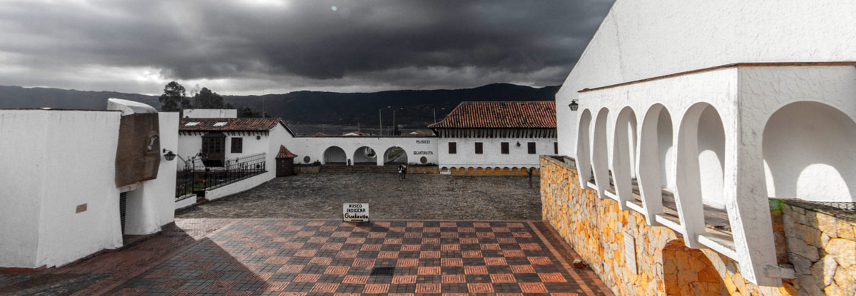 Storm clouds roll over bring white Spanish-style buildings with red roofs - Legend of El Dorado in Colombia