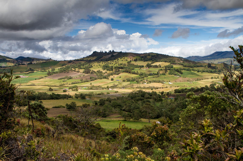 Clouds cast shadows over rolling fields and jungle canopies from the view of Laguna Guatavita on the way to search for the lost city of gold in Guatavita Colombia with kids