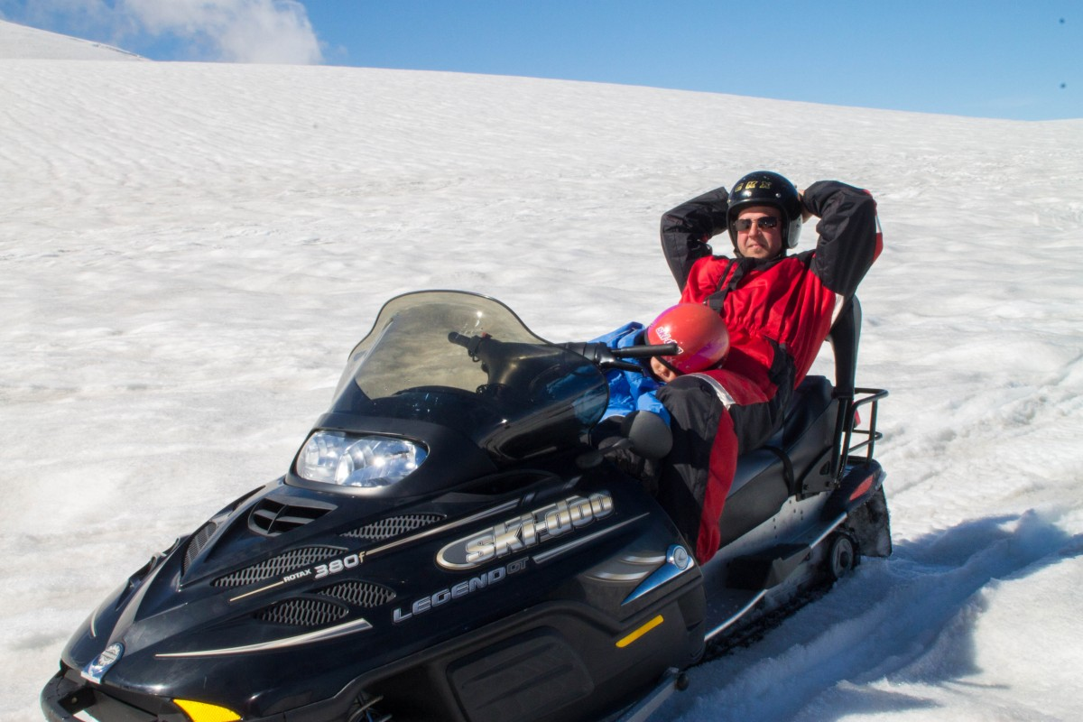 Man sits on a snowmobile on an Icelandic Glacier with a sleeping child in his lap - helping kids find nap time on the road