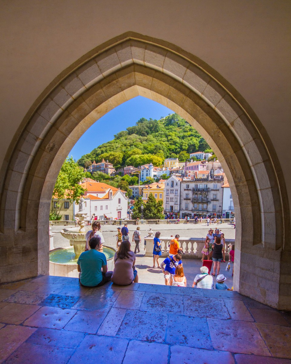 Tourists walking through an historic city viewed through a peaked archway - Sintra, Portugal
