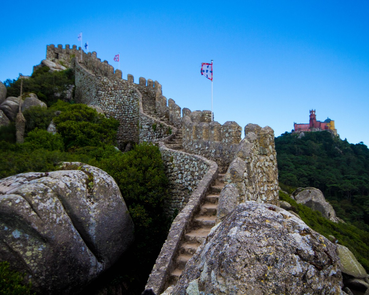 Looking along the wall of a stone castle with a colourful palace in the background - Sintra, Portugal