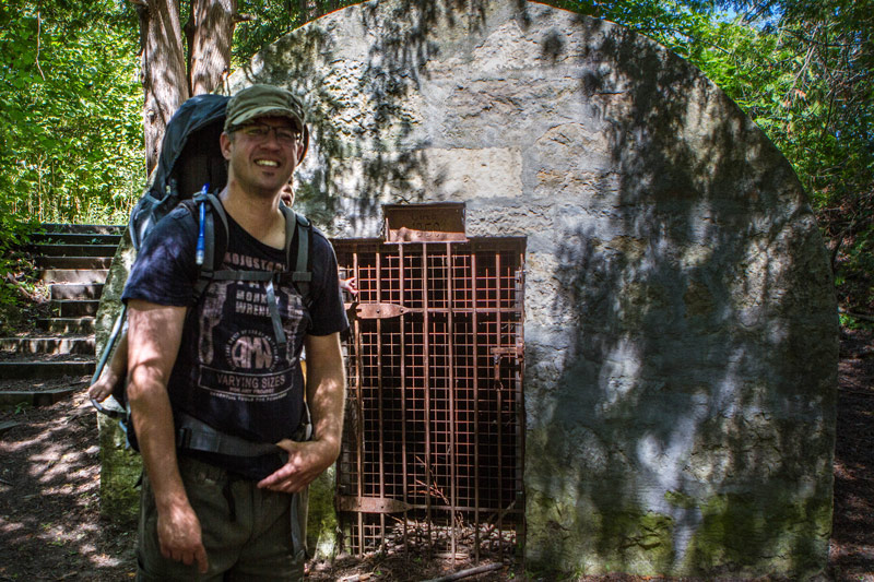 A man wearing a hat and backpack stands next to an ancient explosives vault - Limehouse Conservation Area