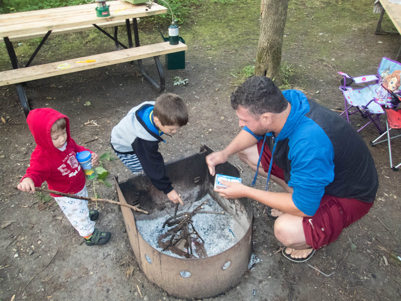 A father and two young boys work to light a fire while camping in Mara Provincial Park with kids