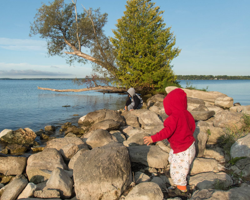 A toddler in a red hoodie and pyjamas climbs over rocks near a lake while camping in Mara Provincial Park