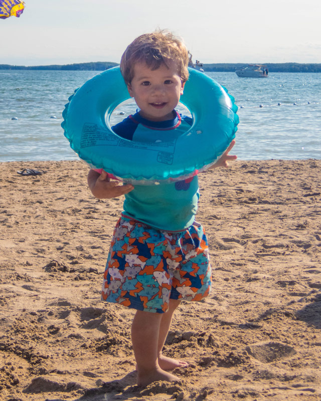 A toddler stands on a beach while holding an inflatable tube like a necklace while camping in Mara Provincial Park with kids