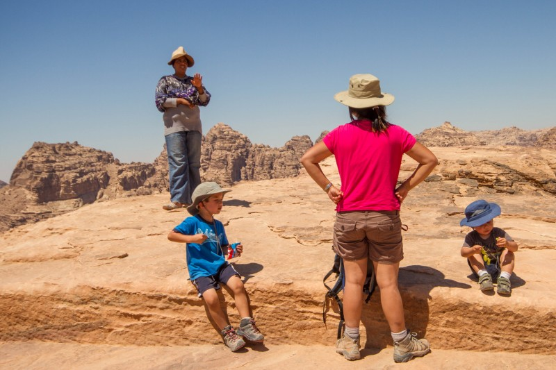Local bedouin woman tells tourists about what can be seen from the High Place of Sacrifice in Petra, Jordan