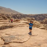 A child walks slowly on top of the High Place of Sacrifice in Petra, Jordan.