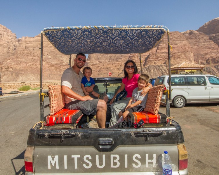 Family of four smiles in the back of a pick up truck in the desert