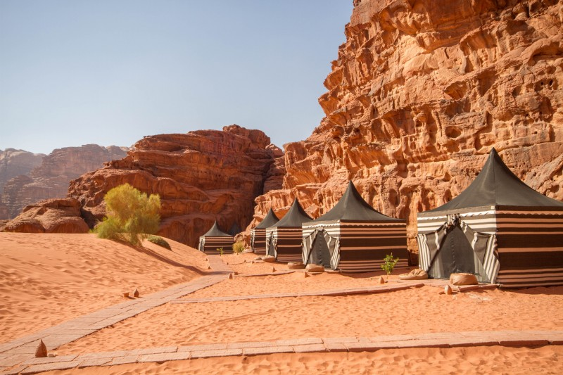 Green and white Bedouin tents sit next to tall cliffs in the desert of Wadi Rum Jordan