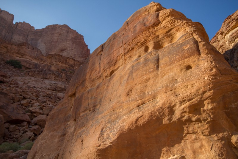 Tall rock in the desert with ancient writing