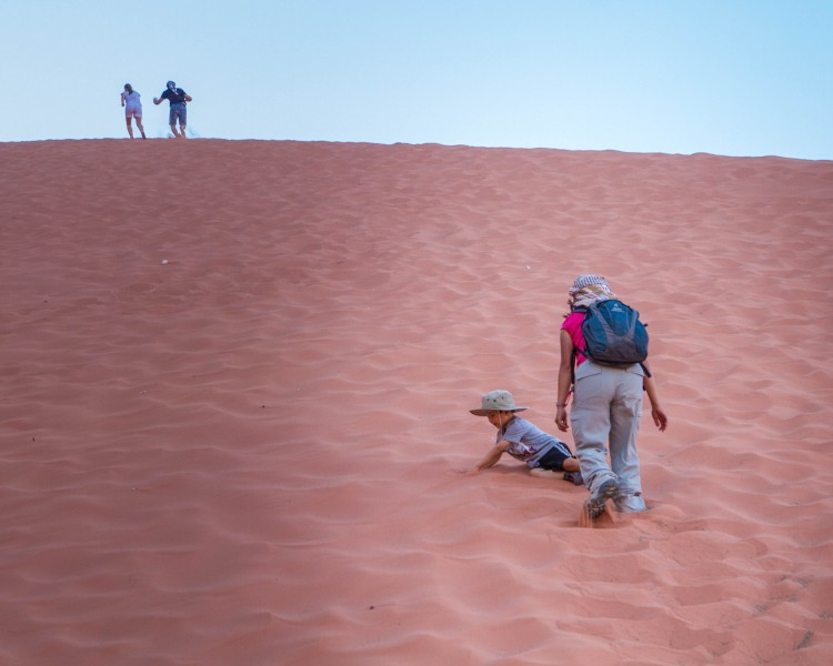 A woman walks with a toddler on a sand dune while her husband climbs to the top during Wadi Rum jeep tours