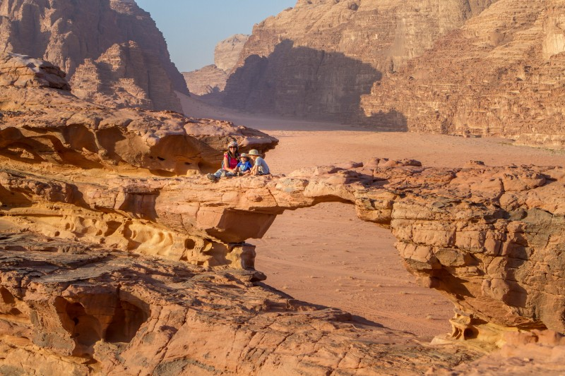 Mother and two young boys sit watching the sun set on a rock arch in the desert
