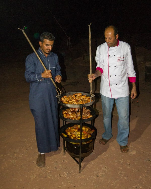 Bedouin cooks bring out food at the Wadi Rum Overnight Luxury Camp