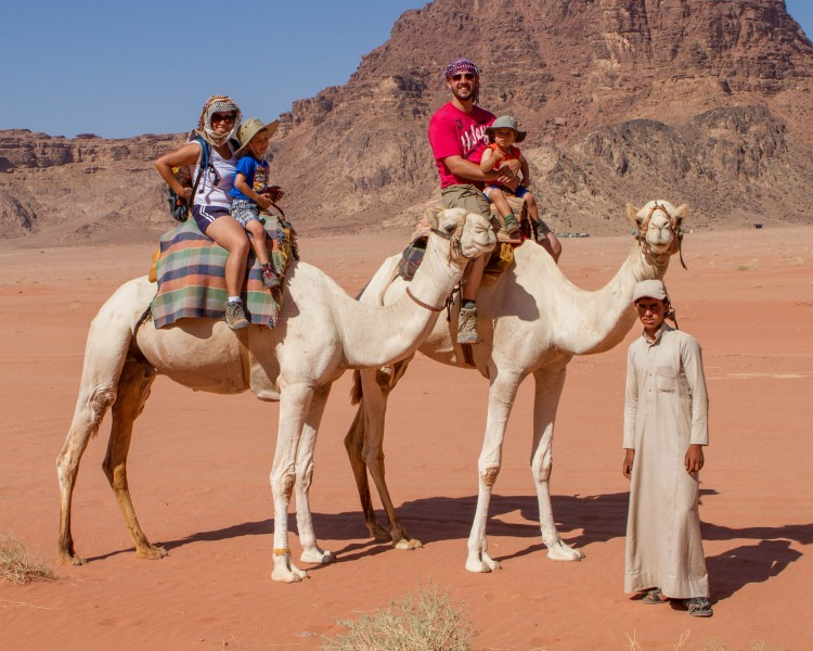The Wandering Wagars ride camels through the Wadi Rum Desert in Jordan