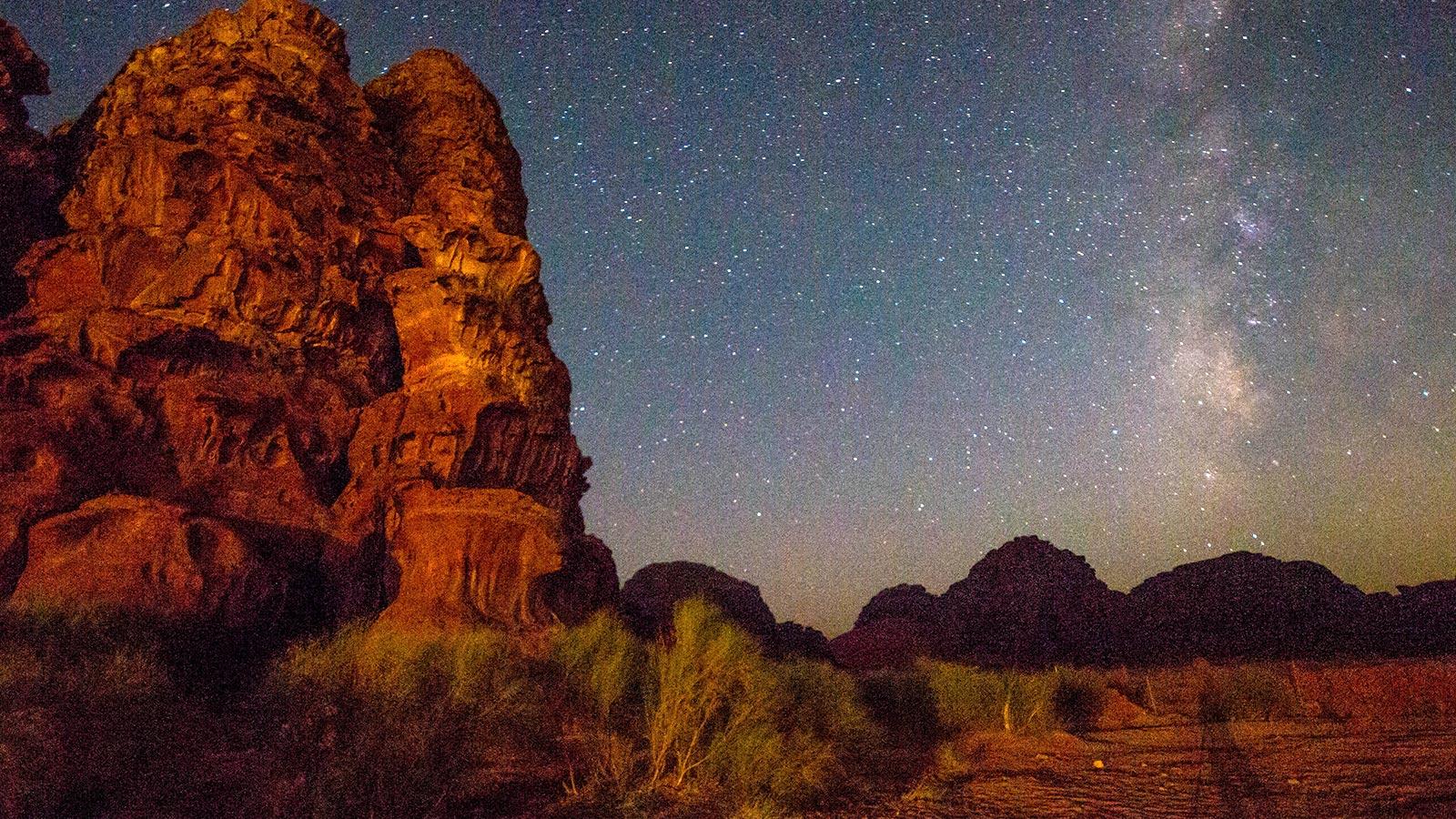 The milky way snakes across the sky of the desert in Jordan as mountains frame the shot