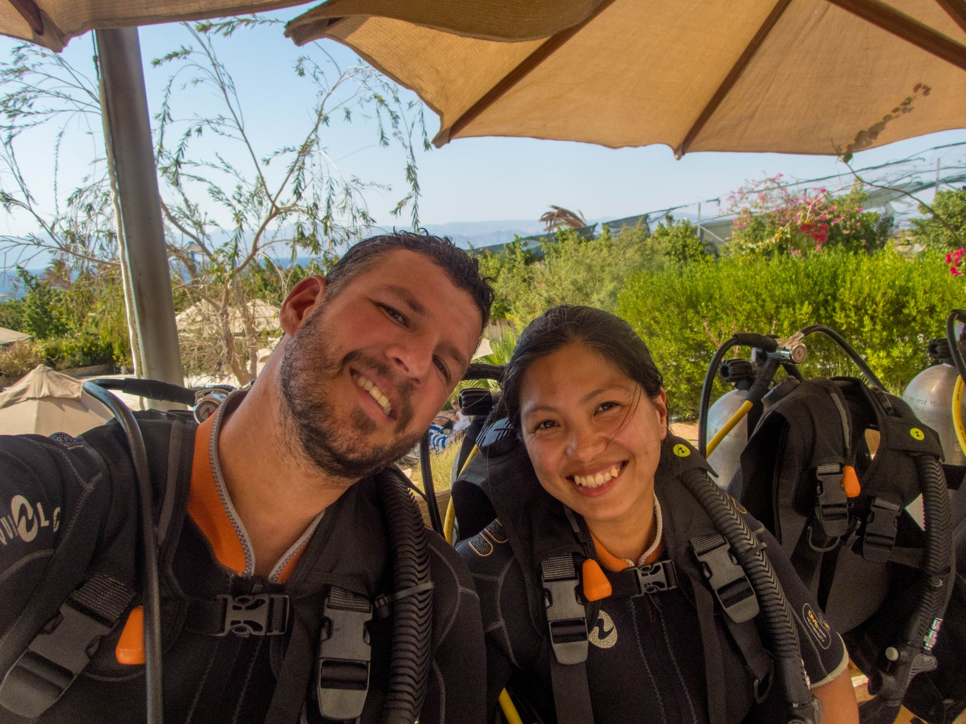 Couple in scuba gear waits to go in the pool to practice their dive skills before going to the Red Sea.