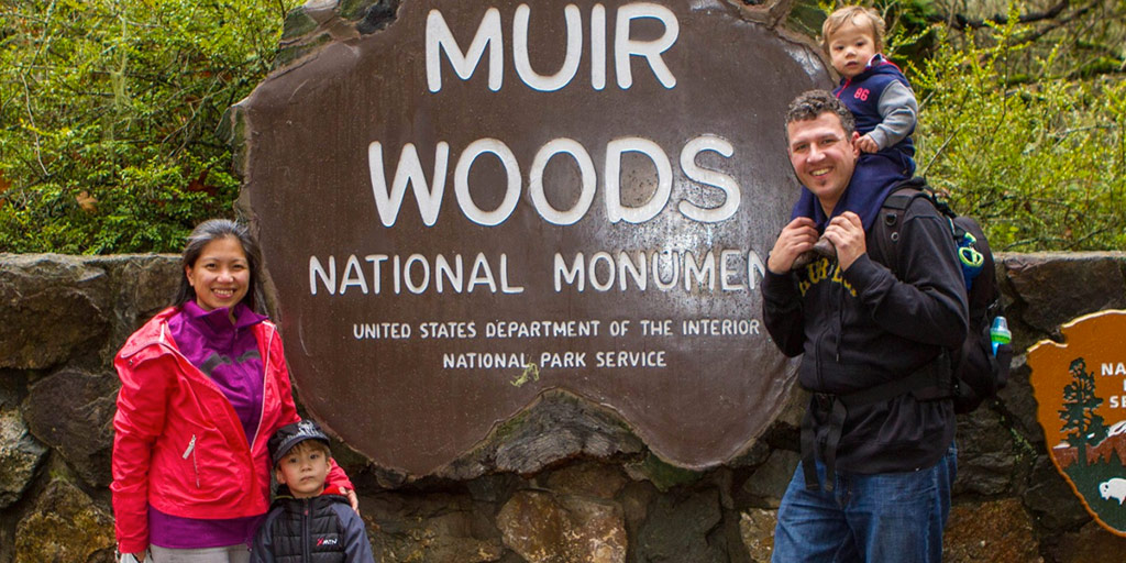 An interracial family stands beside a sign for Muir Woods in California
