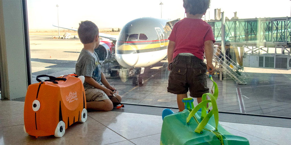 two young boys with cute character luggages look at an airplane through the window of an airport