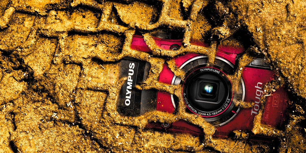 a red camera lies buried in dirt and tire tracks