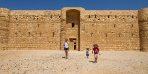 a woman and two young boys walk out of a large desert castle in Jordan