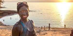A smiling asian woman covered in mud stands in front of the Dead Sea in Jordan at sunset