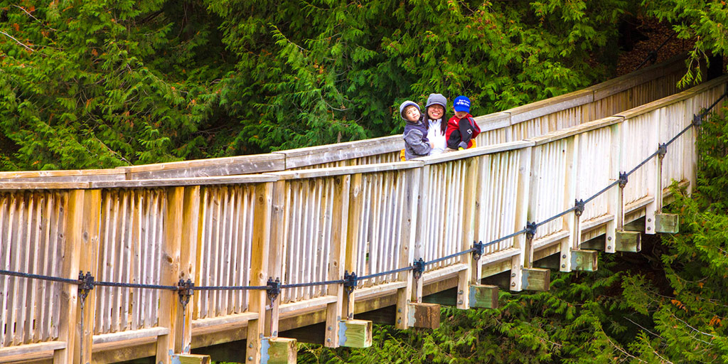 An asian woman holding two young boys smiles while standing on a bridge over a river