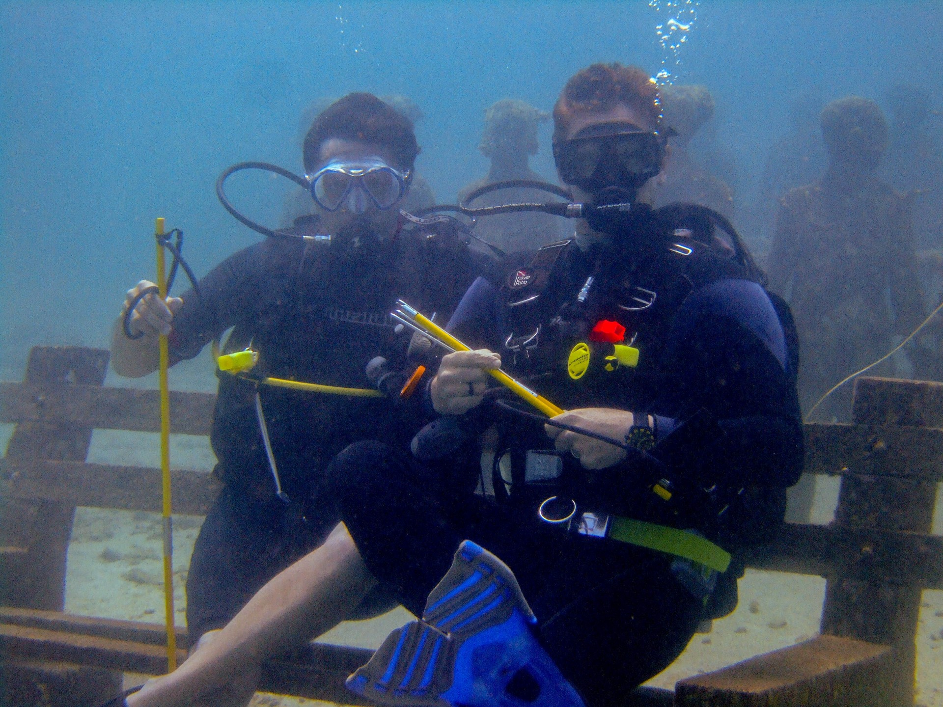 Divers sit on a bench at the Grenada underwater sculpture park