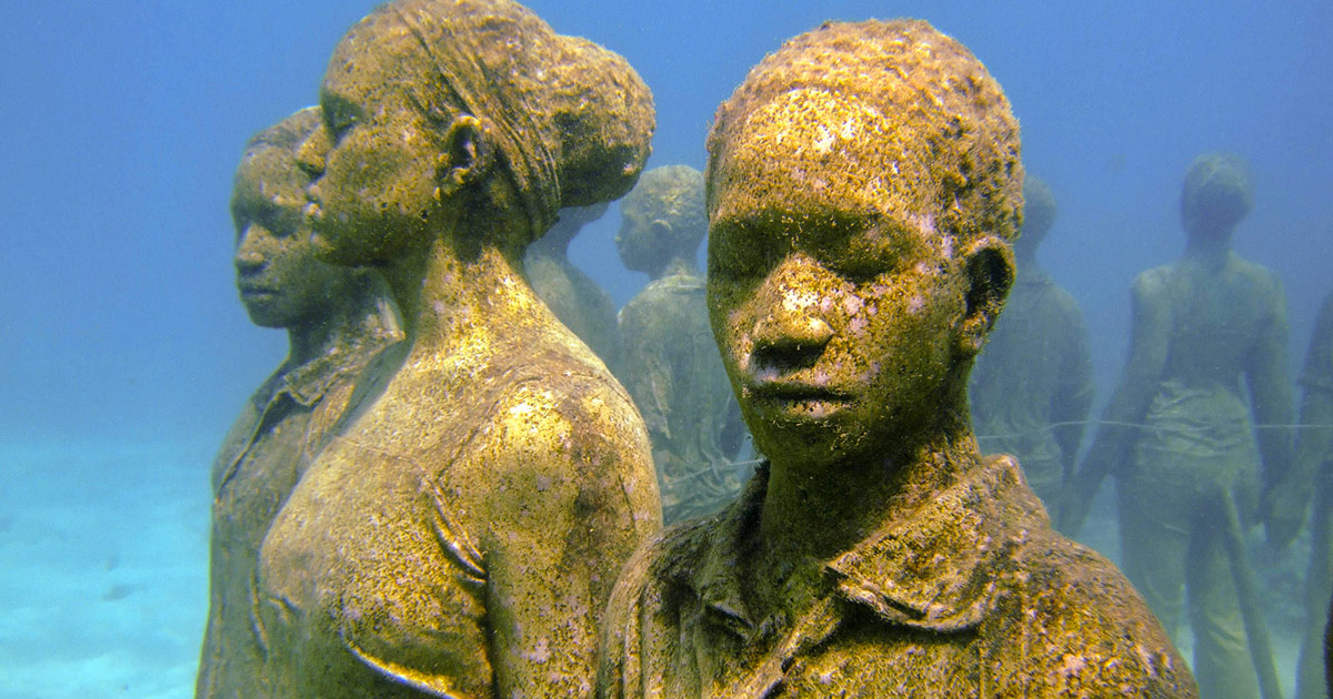 Statues of children holding hands in a circle beneath the ocean