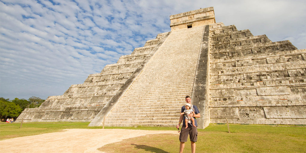 a man holding a baby stands beside a large mayan pyramid in Mexico