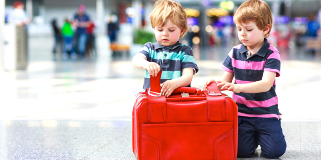 two young children holding luggage in an airport