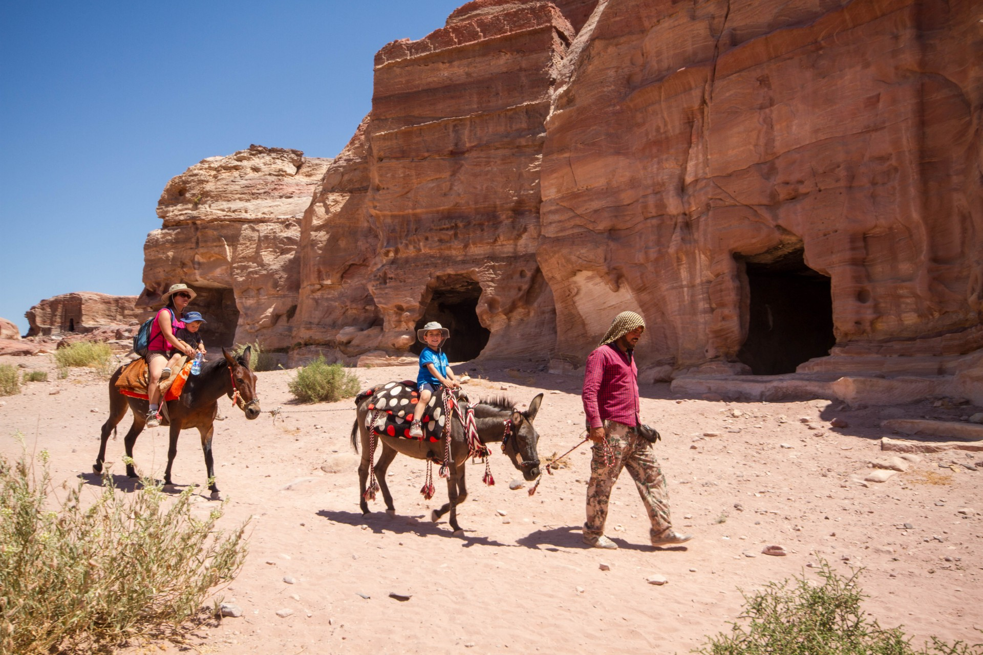 A family rides horses guided by a local in Petra