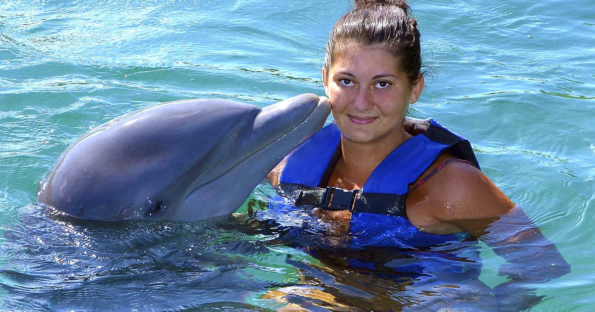 Woman in a life vest getting kissed by a dophin