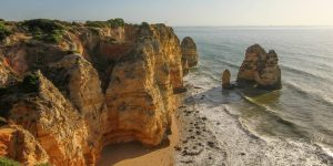 Sunlit cliffs and a beach in Portugal's Algarve