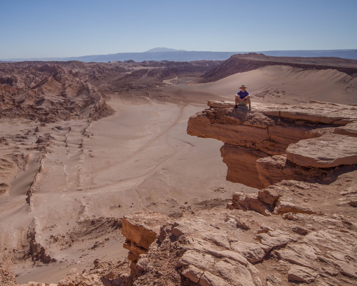 A man sits on a rock outcrop looking out over Valle de la Muerte in Chile