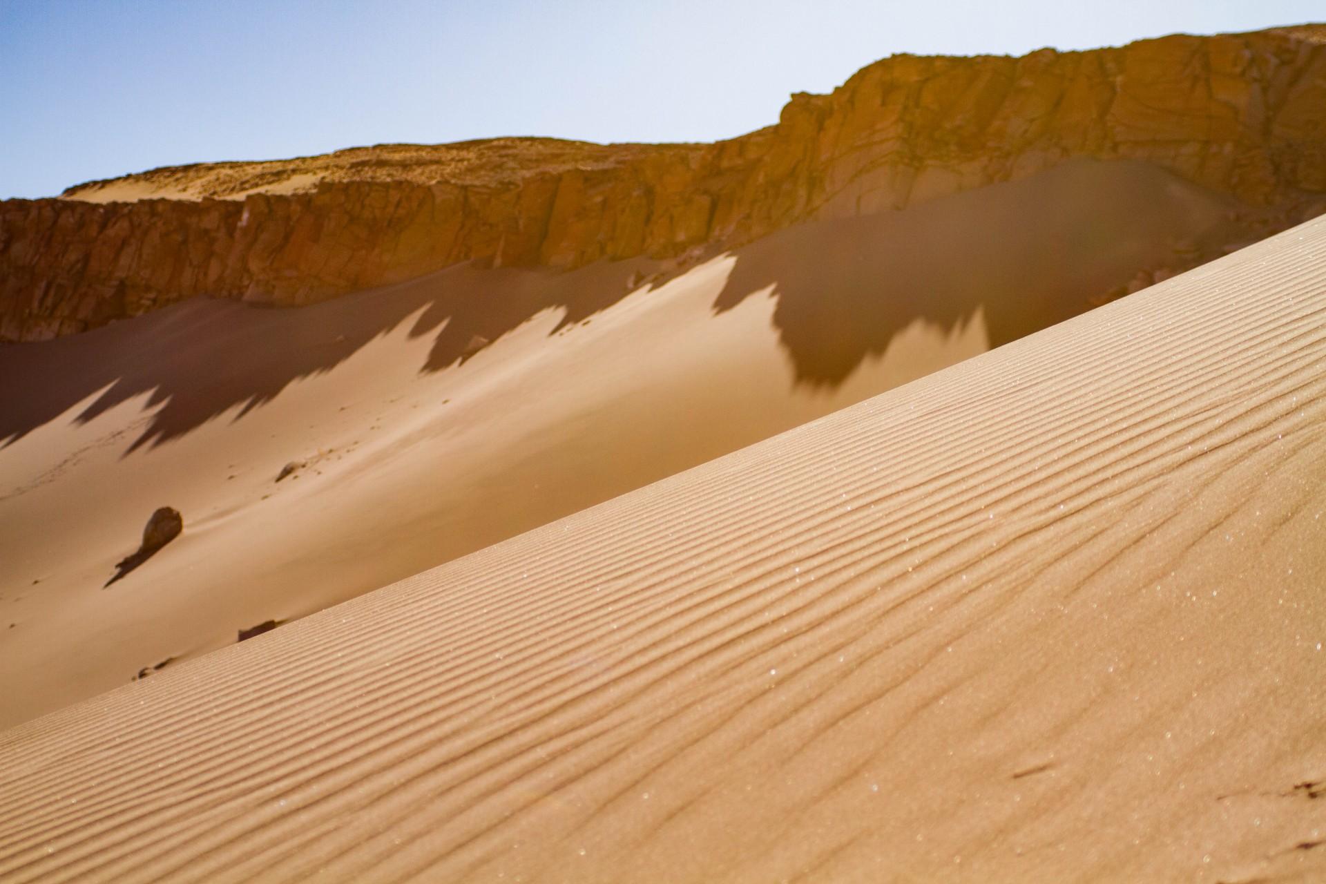 Sand dunes are built up again a rocky ledge in the Atacama desert