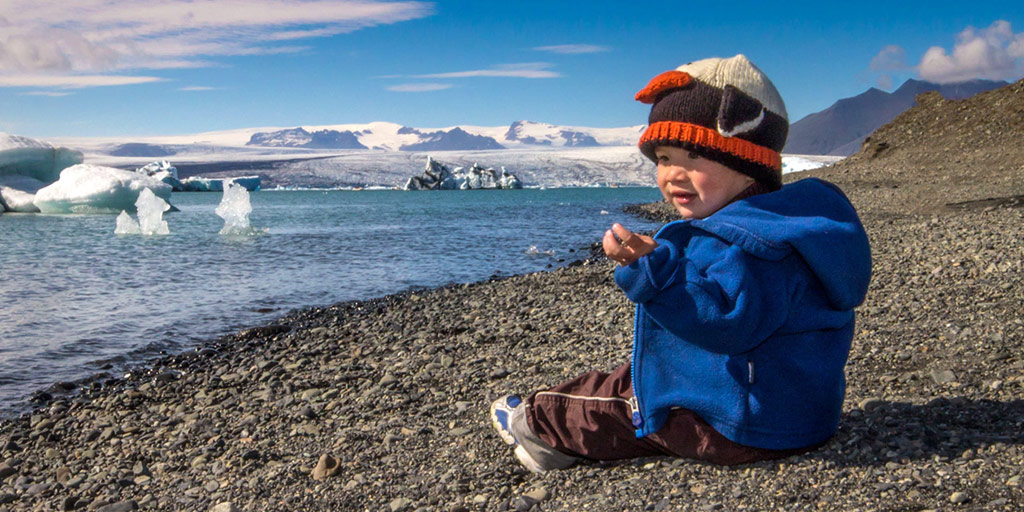Young boy in a penguin hat sitting on a rocky beach looking out at glaciers and icebergs