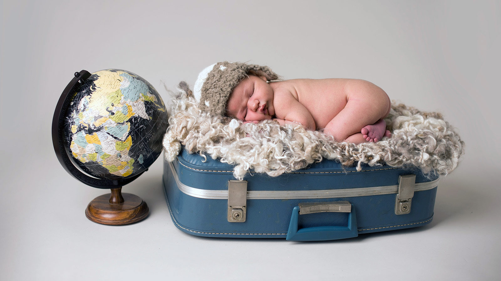 Baby sleeps on a piece of luggage next to a globe - helping kids find nap time on the road