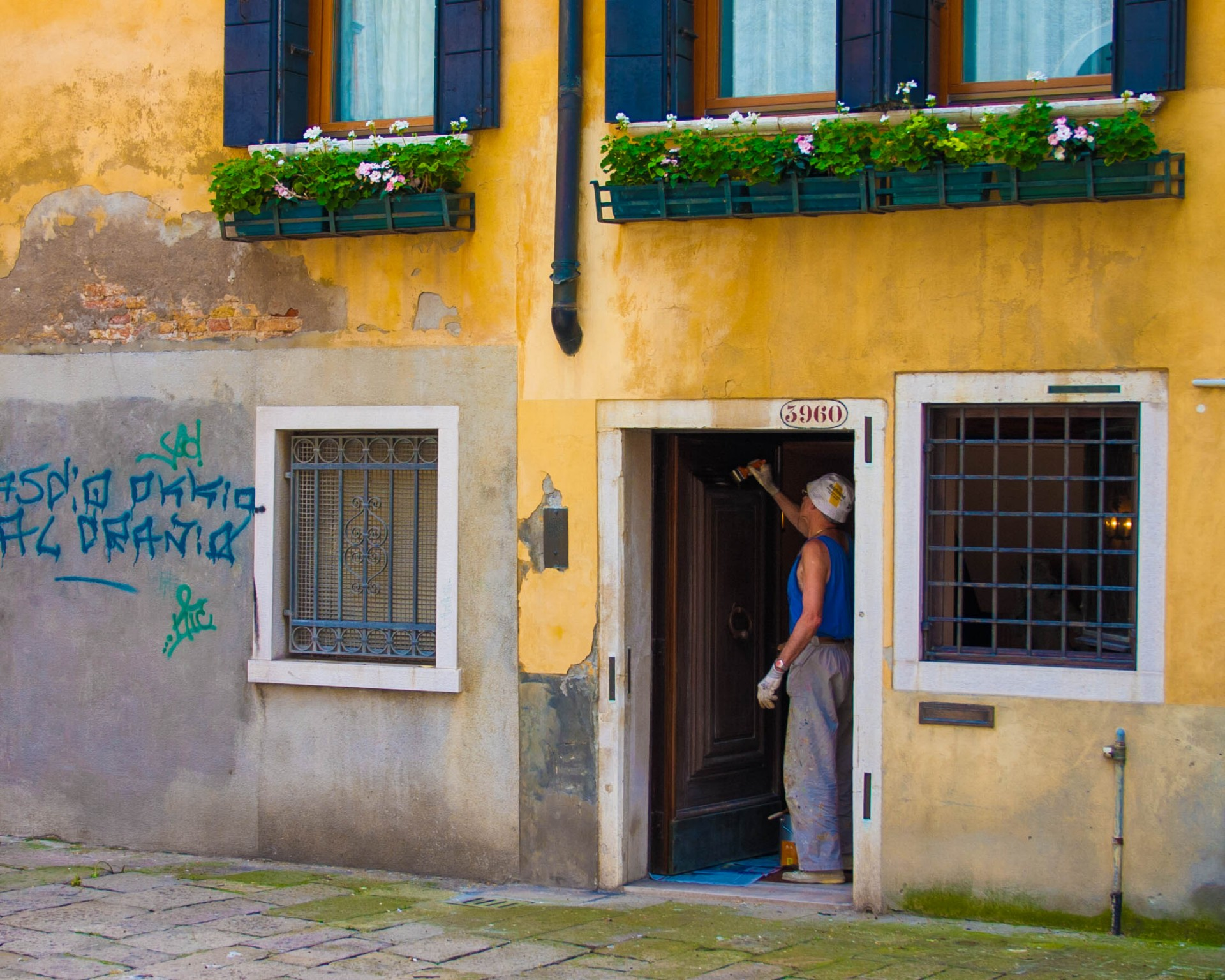 A man paints the white door frame of a yellow house in Venice, Italy - Lost in Venice