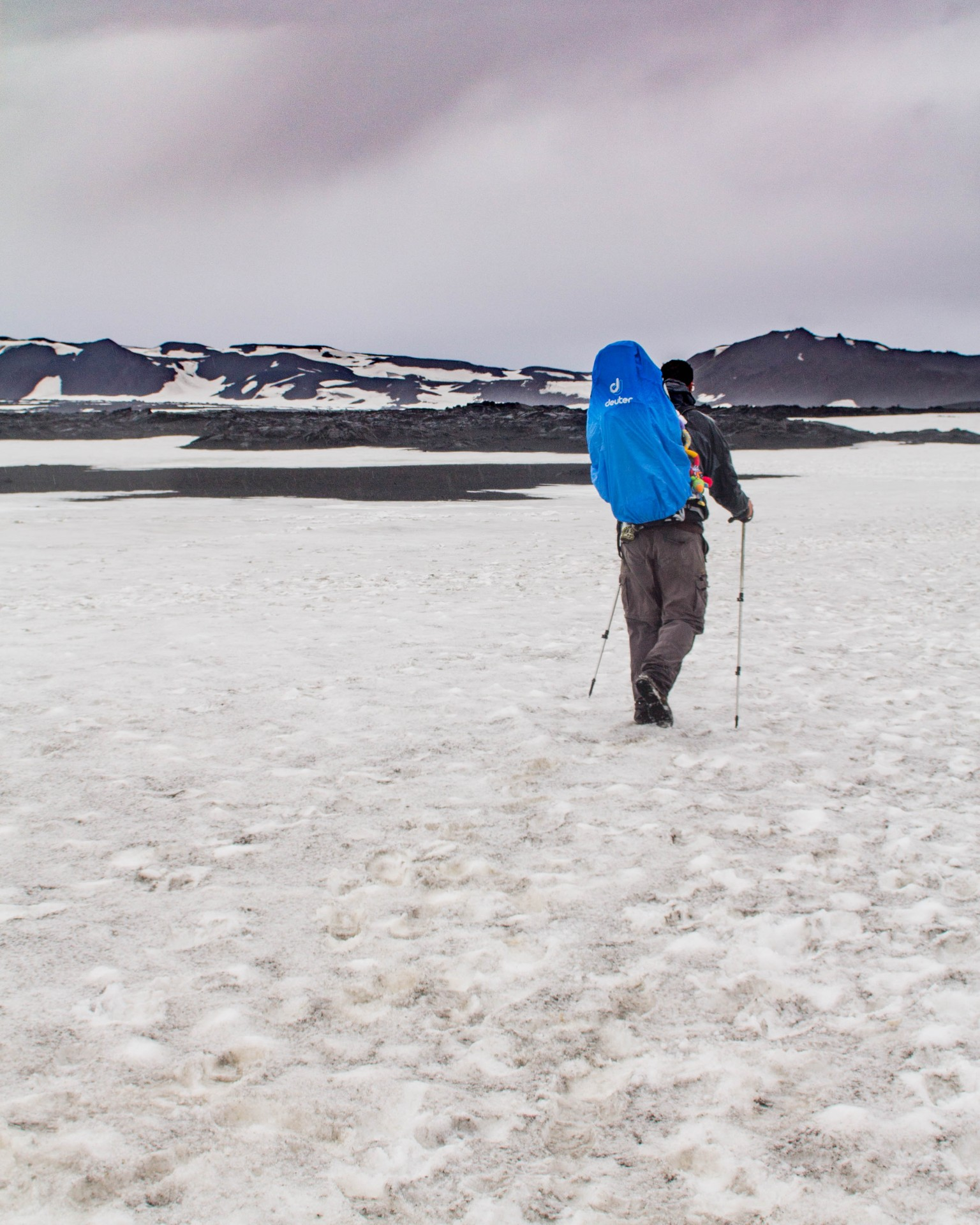 Man hiking through snow with a child in a kid in a Deuter Kid Comfort III Kid Carrier with a blue rain cover