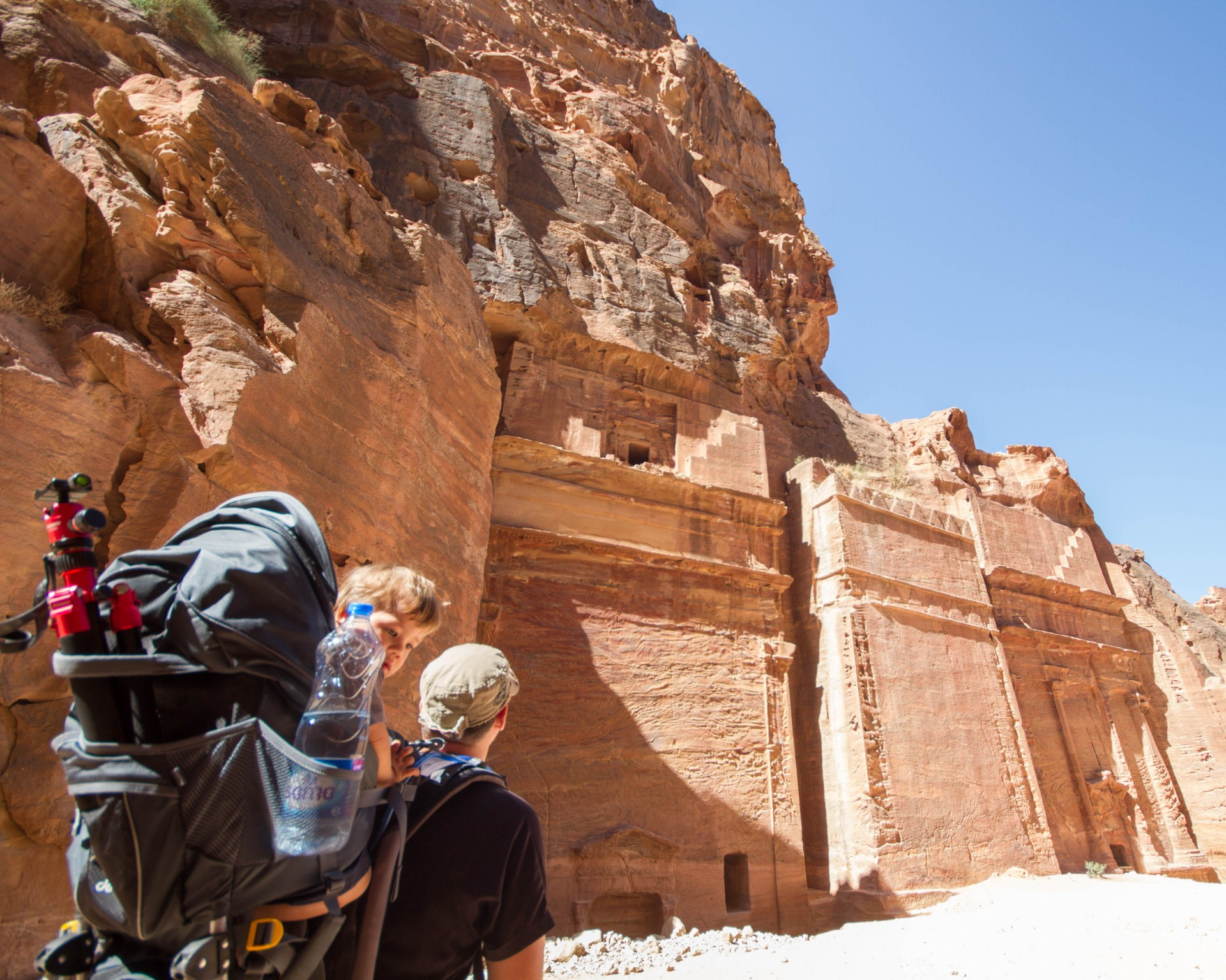 Child looks at the camera from inside a Deuter Kid Comfort III Kid Carrier while his father hikes through Petra Jordan