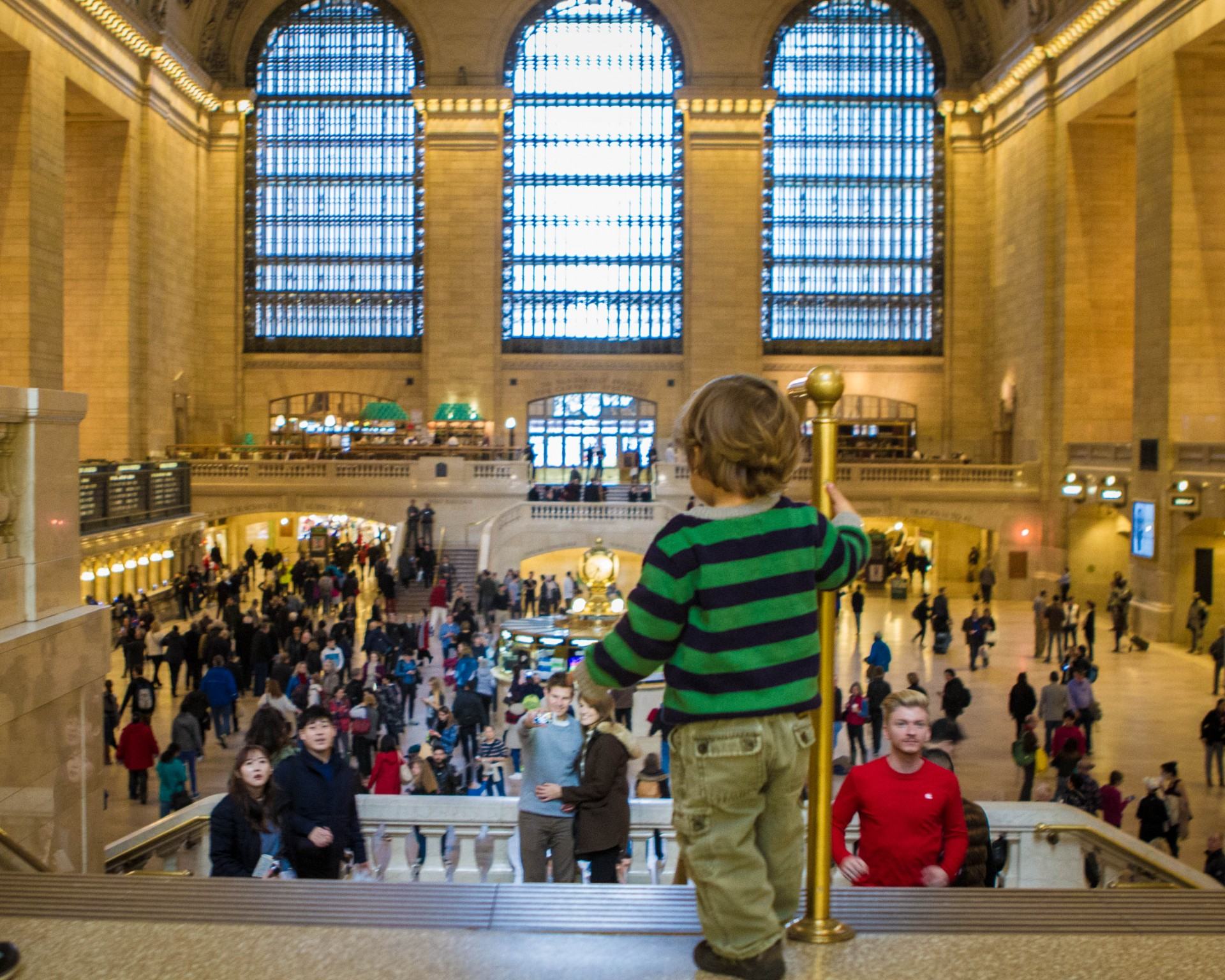 A toddler stands at the top of the stairs looking out over the inside of Grand Central Station in New York City