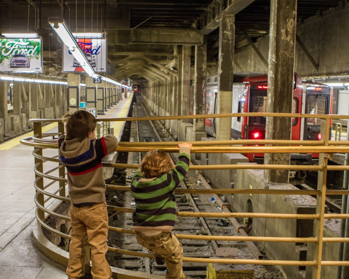 two young boys hang on to a gate while looking at a subway station tracks