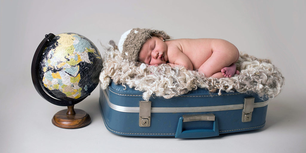 a little baby sleeping on a suitcase next to a globe