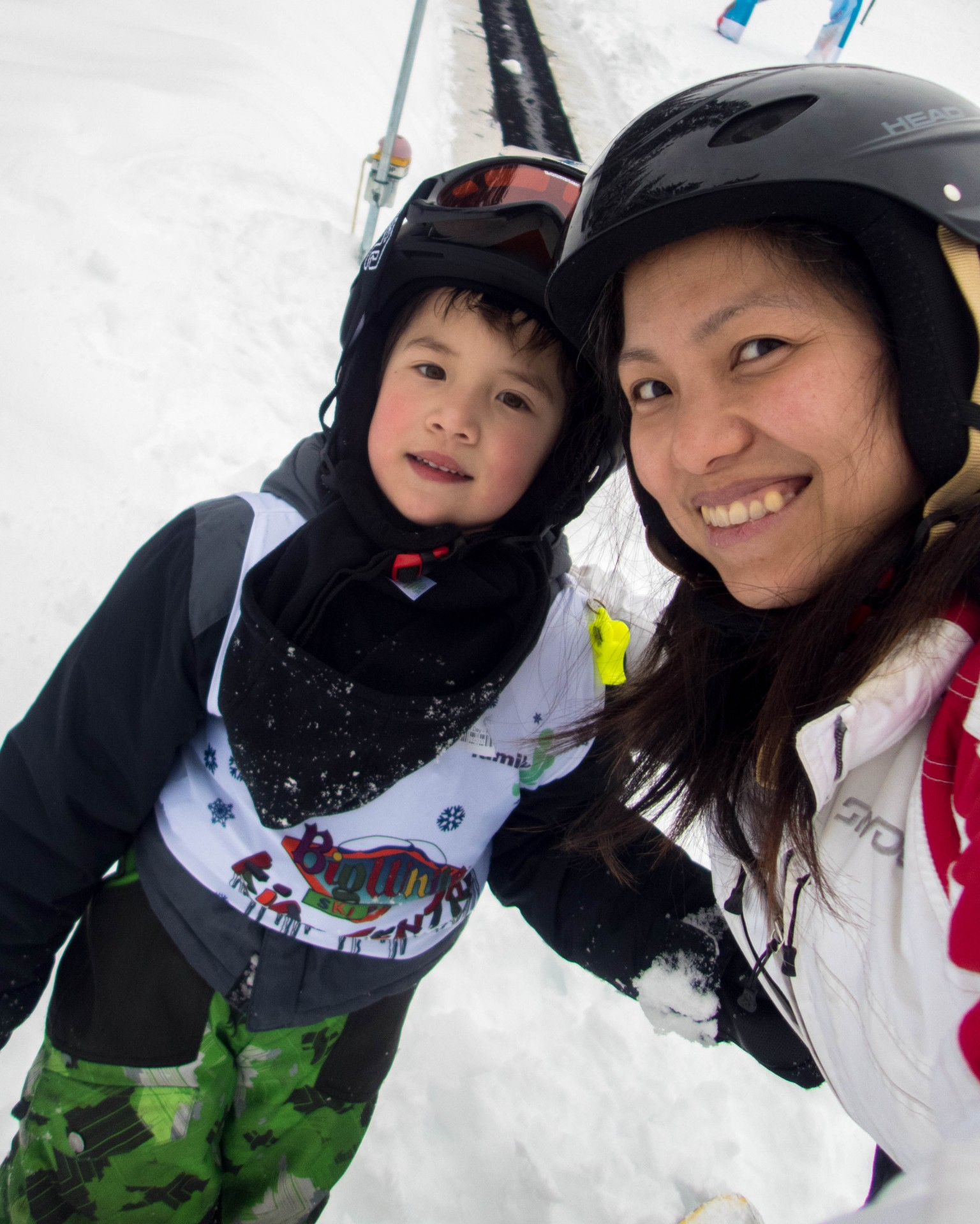 Mom and son in ski outfits smile for the camera - C gets his report card from his instructor at Big White