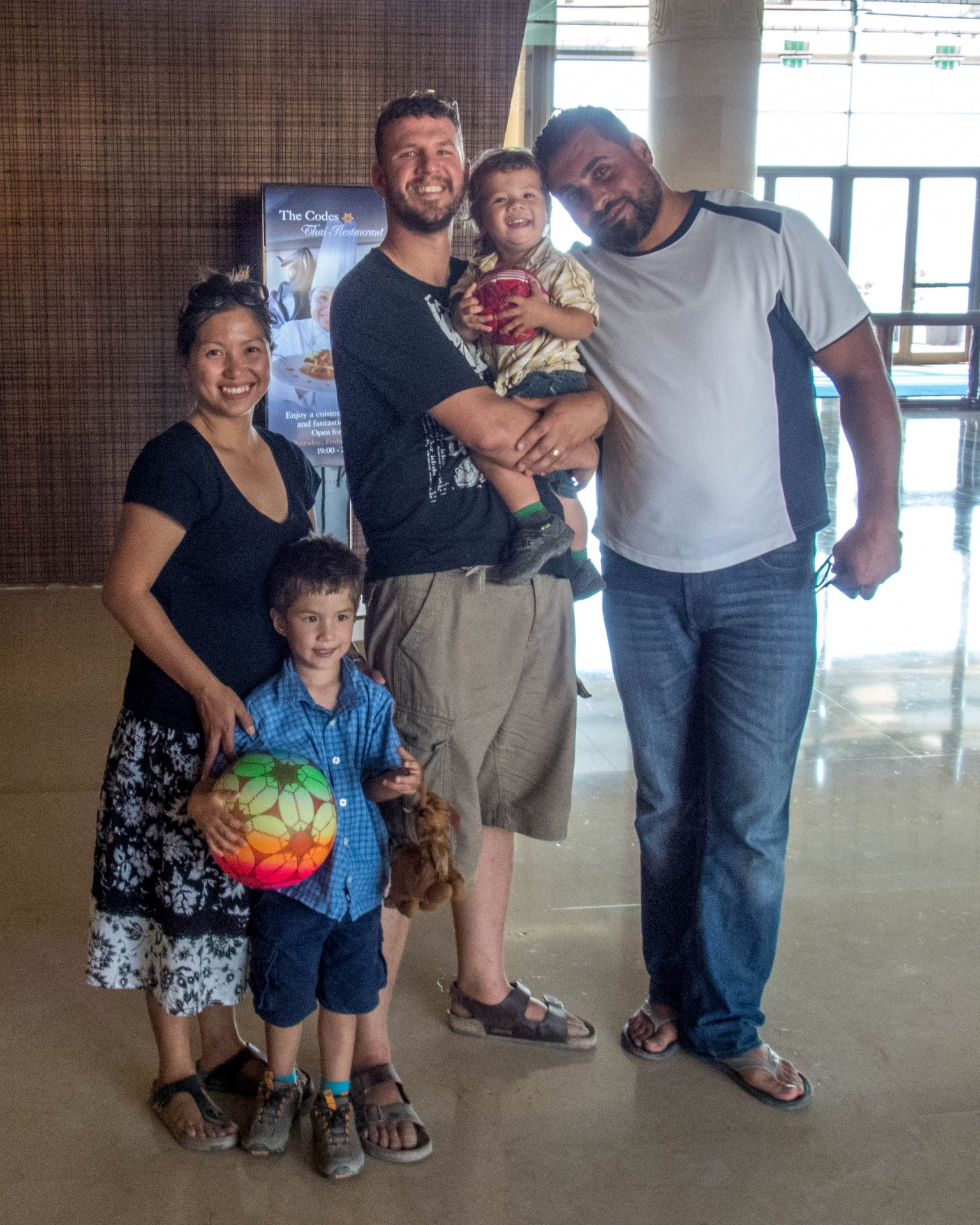 three adults and 2 young children smile in the lobby of the kempinski ishtar hotel
