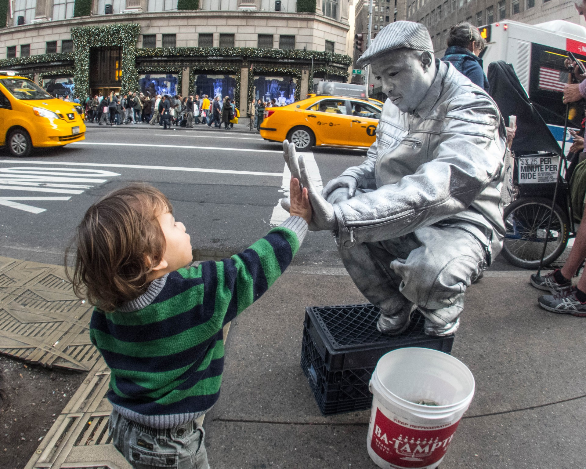 Young boy gives a high five to a street performer wearing silver body paint and a silver outfit
