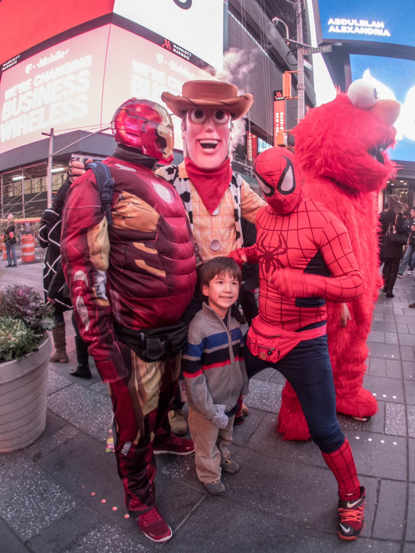 Young boy smiling next to street performers in Iron Man, Woody and Elmo costumes