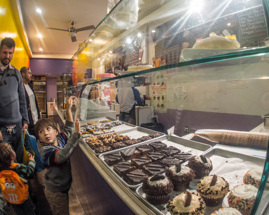 A young boy points at treats in a bakery window