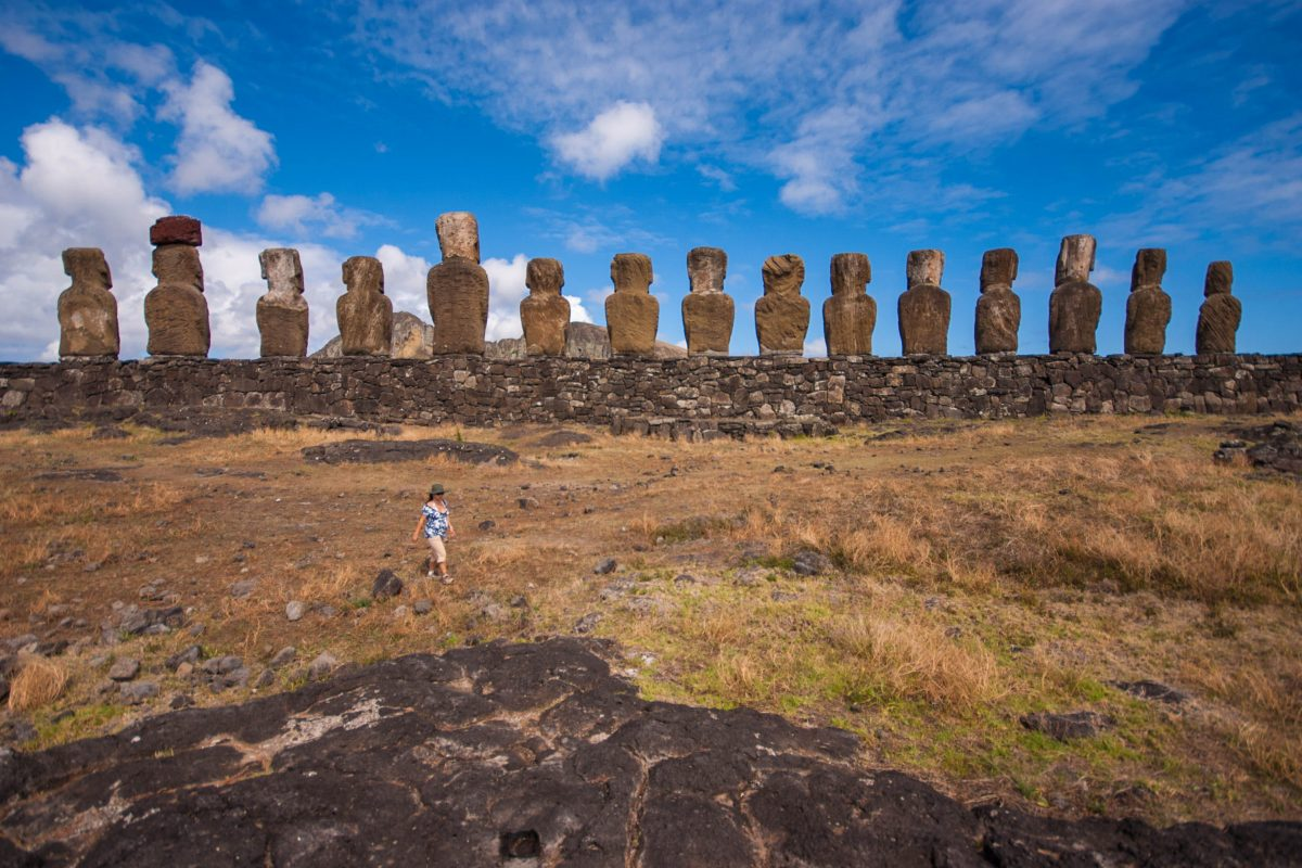 15 moai sit on an ahu looking inland towards Rano Raraku. In the foreground a pregnant woman walks towards the camera, dwarfed by the sculptures