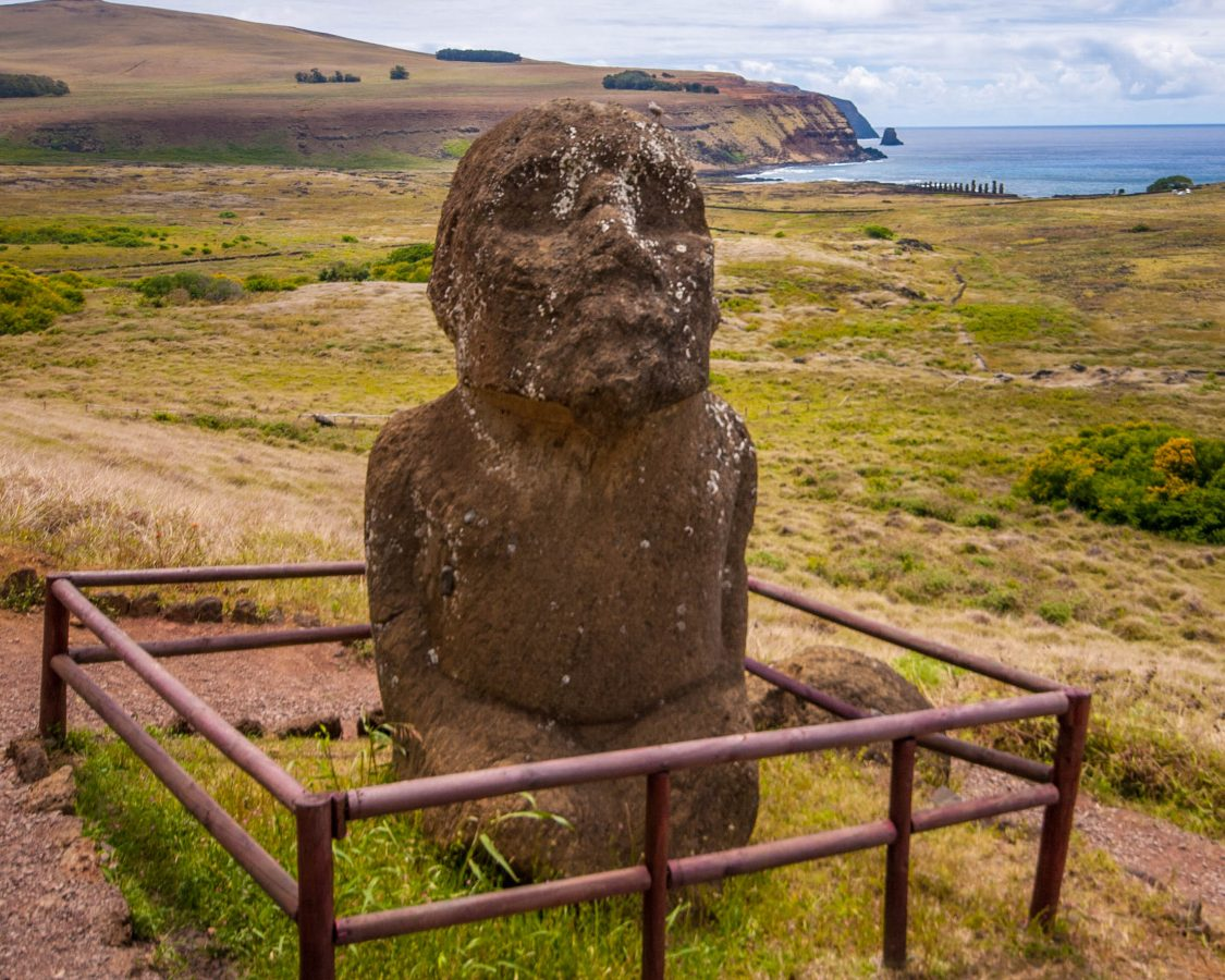 A unique moai sits in a fenced-off area on a mountainside. The moai is kneeling and has a beard. In the background an ahu with 15 moai can be seen.